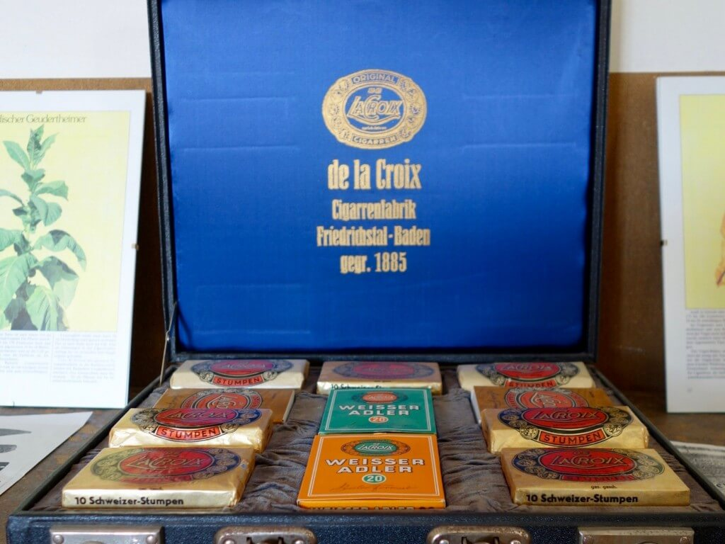 """Gesamtansicht - Der schmale Holzkoffer ist innen mit Samt ausgeschlagen und mit elf Zigarren-Schaupackungen der Firma de la Crox Cigarren aus Friedrichstal versehen. Innen ist der Deckel mit blauer Kunstseide bespannt und zeigt eine ovale Kartusche mit der Aufschrift """"ORIGINAL DE LACROIX sprich: lakroa CIGARREN"""", darunter """"de la Croix Cigarrenfabrik Friedrichstal Baden gegr. 1885"""". Mit Schaukoffern wie diesem priesen Vertreter der im badischen Friedrichstal ans‰ssigen Zigarrenfabrik De la Croix ihre Ware bei potentiellen K‰ufern im Einzelhandel und Gastgewerbe an. F¸r das badische Dorf Friedrichstal dokumentiert der Musterkoffer die Zeit der Tabakindustrie im 19. Jahrhundert, in der Baden neben Preuflen das grˆflte Tabakanbaugebiet Deutschlands darstellte. Die in der Markgrafschaft Baden-Durlach und dem Bistum Speyer aufgenommenen Hugenotten hatten hatten Tabaksamen und Kenntnisse ¸ber den Tabakanbau aus Frankreich und ihrem zeitweiligen Aufenthalt in der Pfalz mitgebracht und schufen damit die Voraussetzung f¸r die weitere Verbreitung des Anbaus in Deutschland. Eine von ihnen gez¸chtete Tabaksorte wurde nach der neuen Heimat """"Friedrichstaler"""" genannt."""